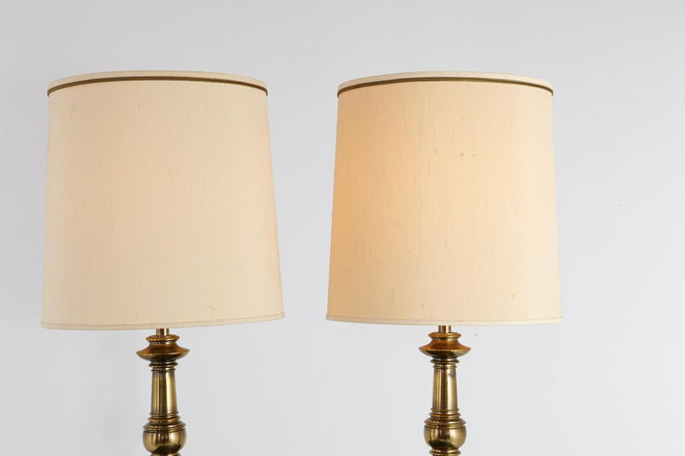 Pair of traditional Stiffel burnished brass table lamps with the original ivory colored drum shades,  circa 1950-1960s. Very heavy, solid brass quality. One lamp has some tarnish on the base, both lamps have a natural brass patina,  which can