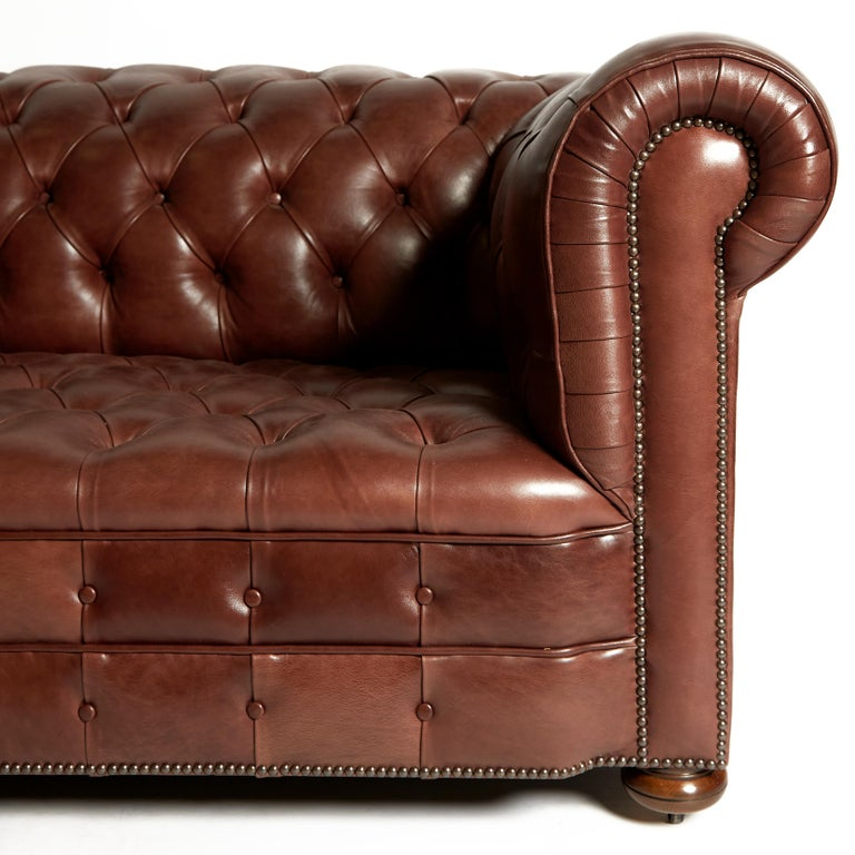 This very handsome and oversized pair of traditionally designed Chesterfield sofas are upholstered in a deep buttoned chocolate brown leather. The sofas feature wide roll back arm rests and stand on mahogany bun feet. Each sofa measures 104 in -