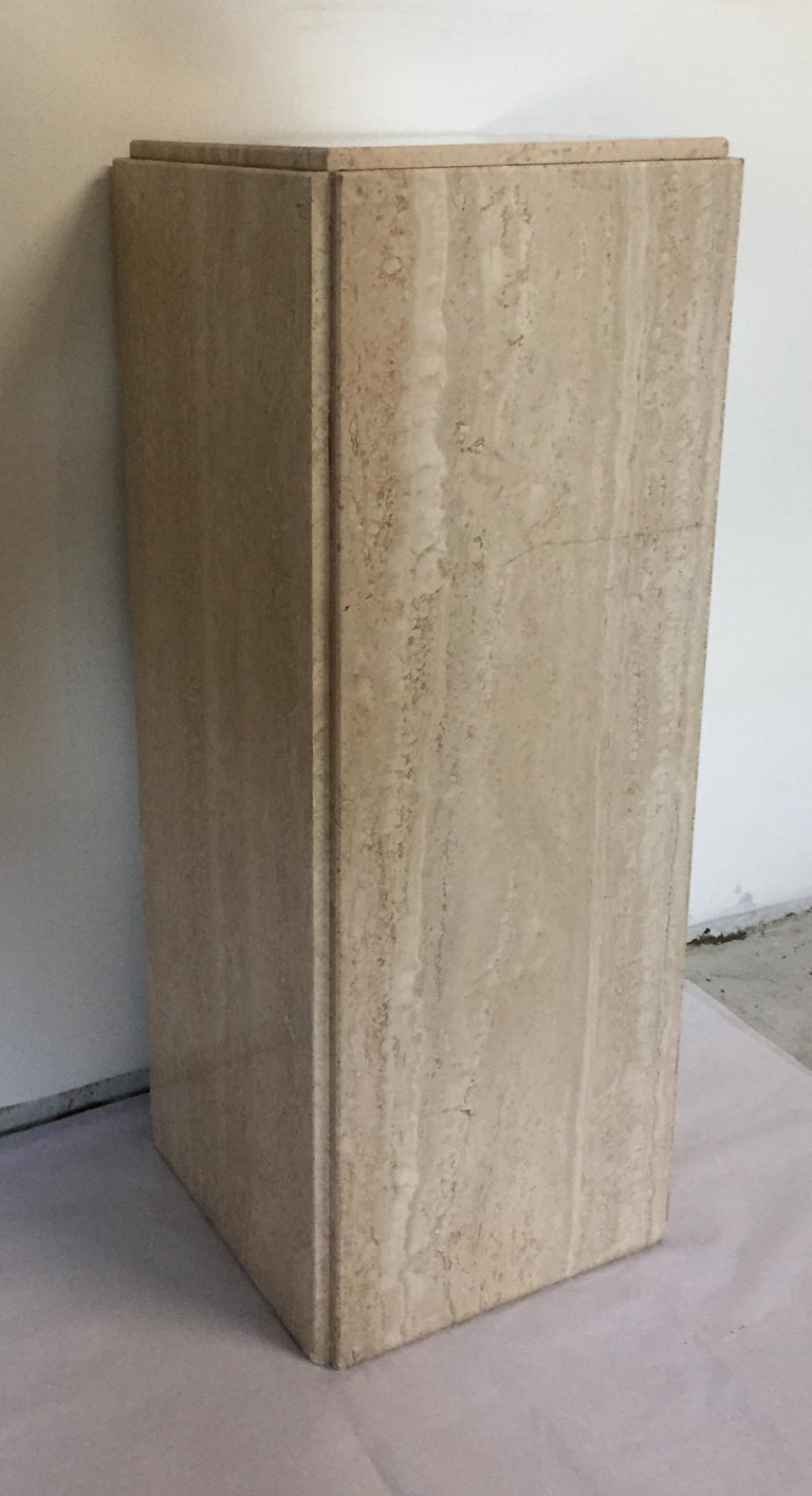 Pair of pedestals in beige travertine. Grinds along each side from the base to the bottom and around the top. Elegant bases.