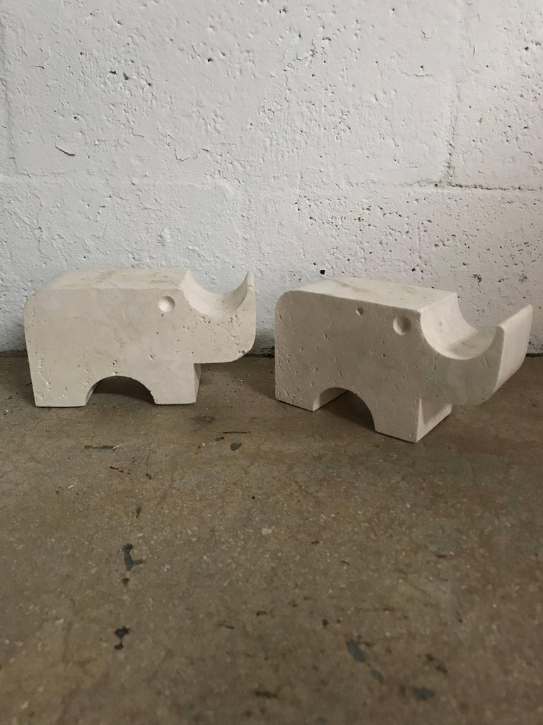 Solid pair of Rhino sculpture statues or bookends rendered in carved travertine, designed by Flli Mannelli for Raymor, Italy, 1960s, Signed.