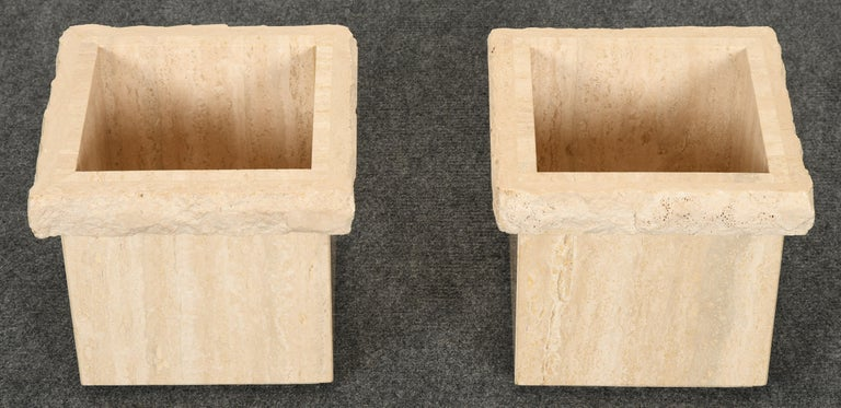 A unique pair of Travertine Roche Bobois style marble planters. These planters have a rough-hewn top edge with a polished Travertine base.  Dimensions: 11.5