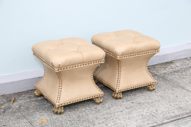 Pair of tufted leather ottomans finished with nailheads and solid brass claw feet.