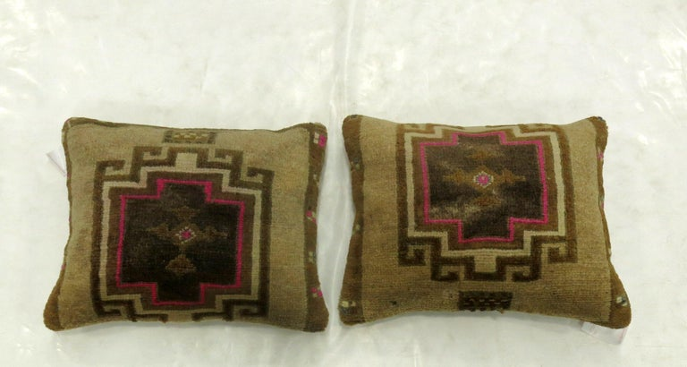 Two pillows made from a Turkish rug with pops of pink. Measuring 16