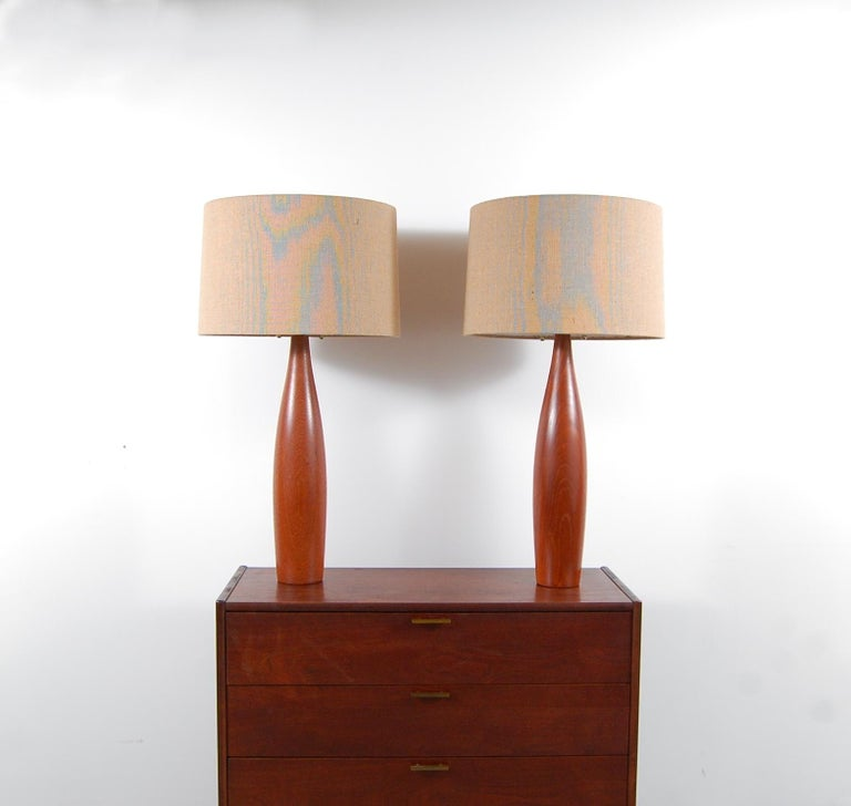 Pair of solid teak lamps by Esa Møbelvaerk, Denmark, circa 1958. Lamps have been completely re-wired for safety, and new top of the line brass hardware added, as well as brand new burlap shades. Lamps have also been dressed with brown, cloth wrapped