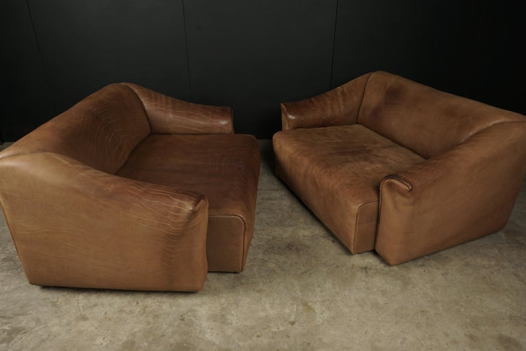 Pair of two seat sofas by De Sede, Switzerland, circa 1960. Original, very thick buffalo leather upholstery. Seats extend about 5-6