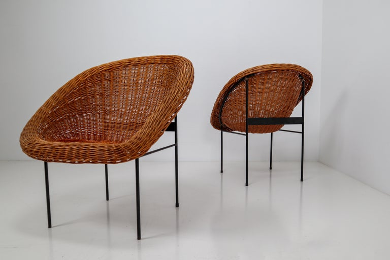 Pair of two wicker midcentury easy chairs designed and produced in France during the 1960s. The chairs are made from handwoven wicker for the seat that is formed into a basket. The frame is made of black lacquered steel. They are comfortable to sit