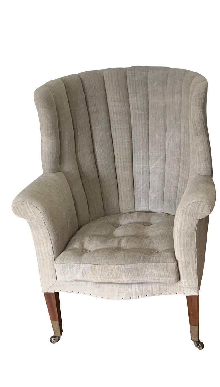 19th century pair of exceptional upholstered English barrel shaped high backed armchairs. The seat back has a vertical rib tufted design. The separate padded seat cushion has a toggle tuft decorative detail and is very comfortable. Sabots are