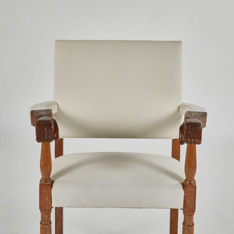 A pair of upholstered armchairs with carved arms as hands, originating in England, circa 1880.