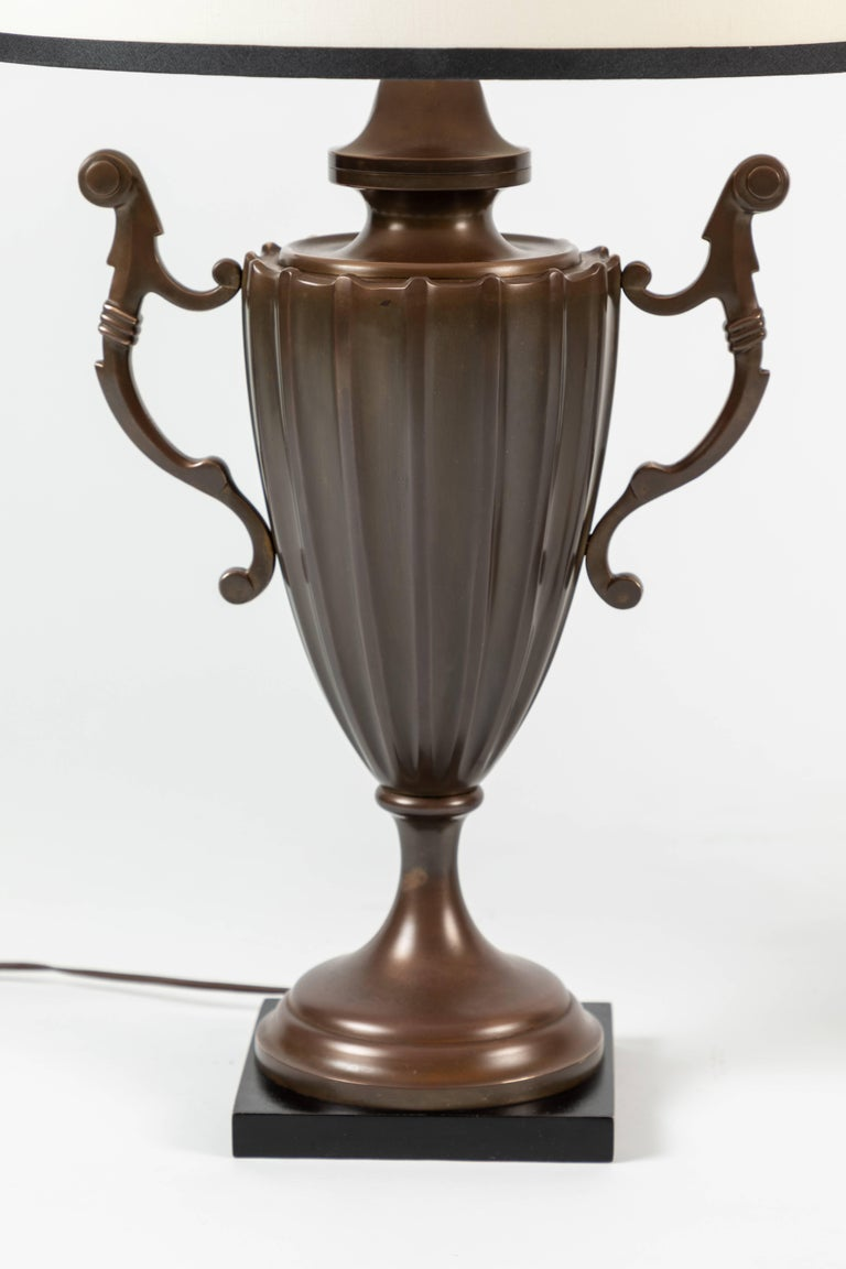 Manufactured by Chapman Manufacturing Company, these table lamps resembles a fluted English urn (or an Accolade cup trophy) made from solid brass.   The shades are newly designed, and custom made.