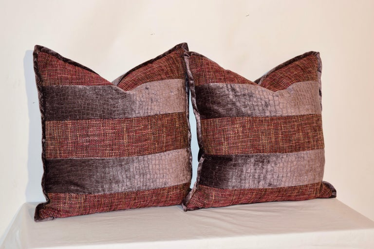Handmade pillows made from dusty grape velvet and woven multicolored fabrics with a contrasting velvet welt. The covers have hidden zippers and the inserts are removable. Dry clean only.