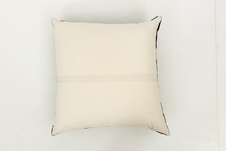 Pair of velvet throw pillows in a cream and black geometric design. Feather and down inserts with a cream fabric back.