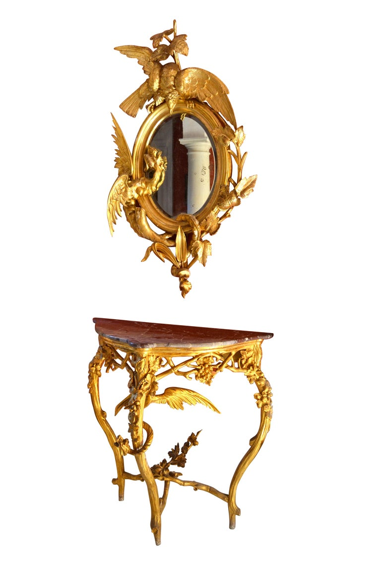A rare, unique and dramatic pair of Rococo style marble topped giltwood triangular shaped consoles and complimentary slightly elliptical giltwood mirrors. The four pieces are believed to be northern Italian most likely from the Venetian region. The