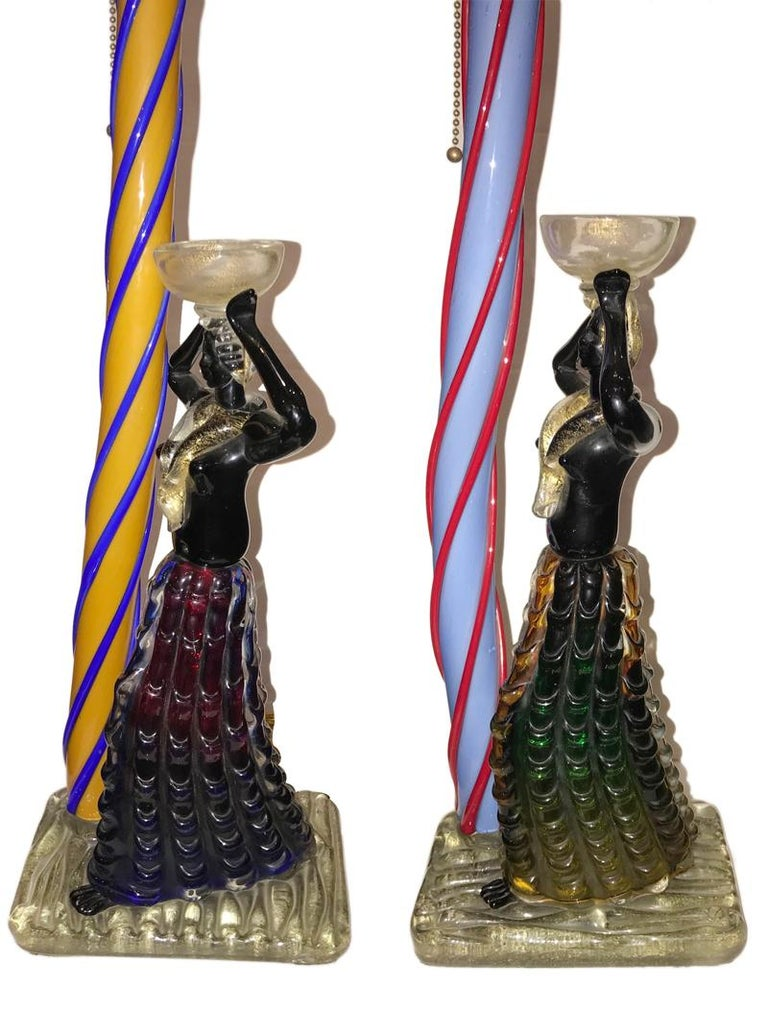 A very unique pair of circa 1940's Italian hand-blown figural art glass table lamps in the form of Carnival characters standing next to Venetian columns.