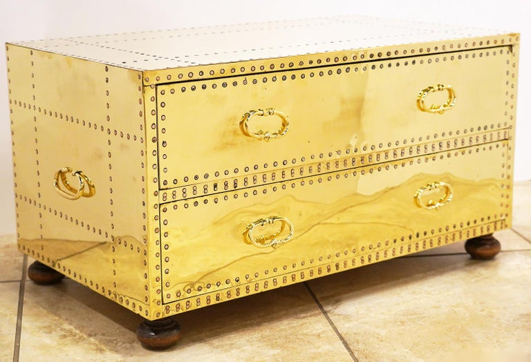 A pair of spectacular polished brass clad and copper nail studded 2-drawer chest on turned wood feet by Sarreid, Ltd. The chests have been recently professionally polished and clear coated. Made in Spain in the 1970s and in excellent condition.
