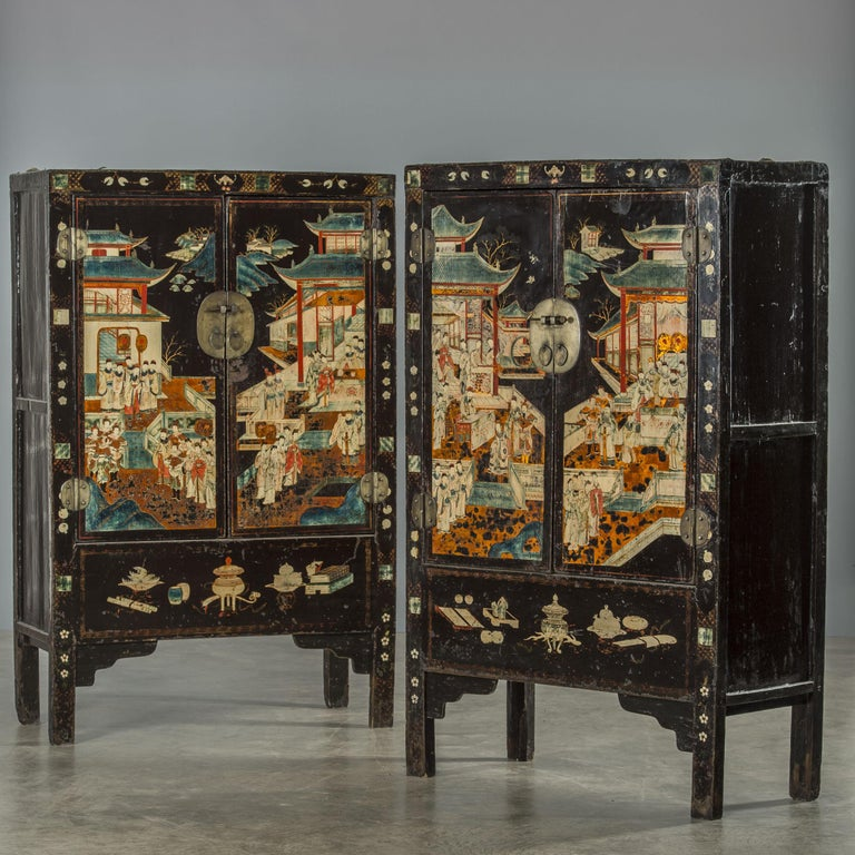 Pair of unusually beautiful cabinets in black lacquer with well-preserved original decorations in polychrome, showing houses and people. The cabinets are rarely seen today. Dating 1700s Qing dynasty. From Shanxi province in China.