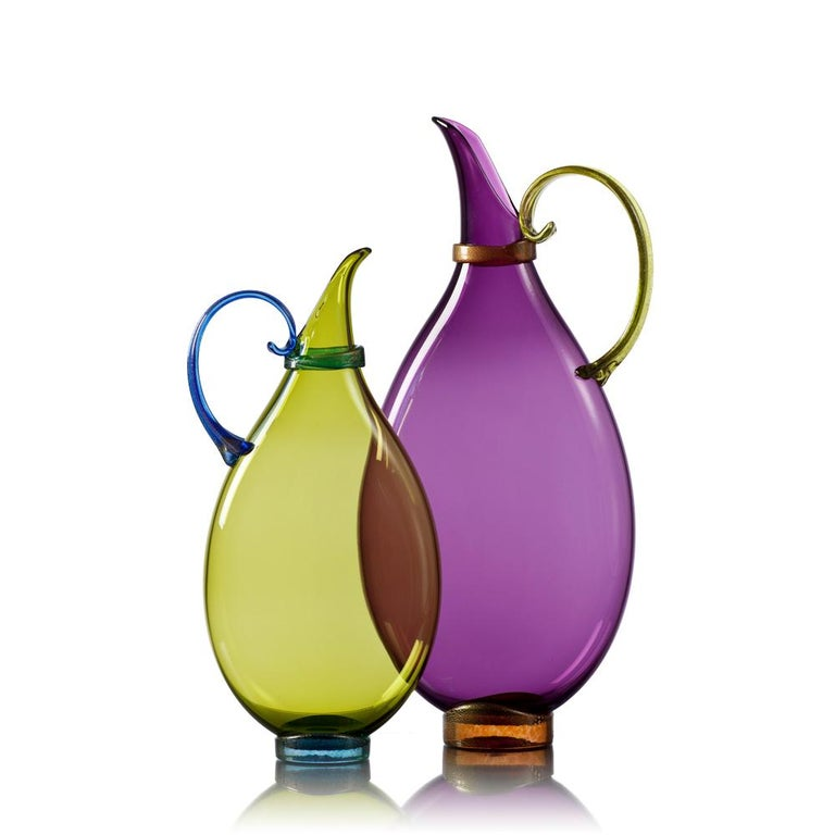 Assemble a set of two hand blown glass statement vessels in luminous glass hues with gold-leaf details. Each decorative vessel is flattened during the glassblowing process to inspire layered displays of translucent color. Choose from a complete