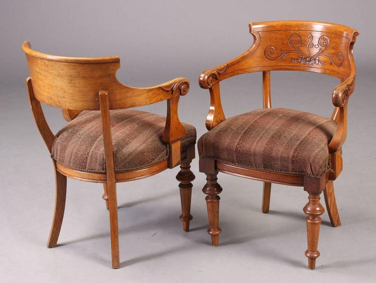 Handsome pair of Victorian period armchairs in oak with carved foliate scroll on the back. Turned front legs and sabre back legs. Good desk chairs. More available.