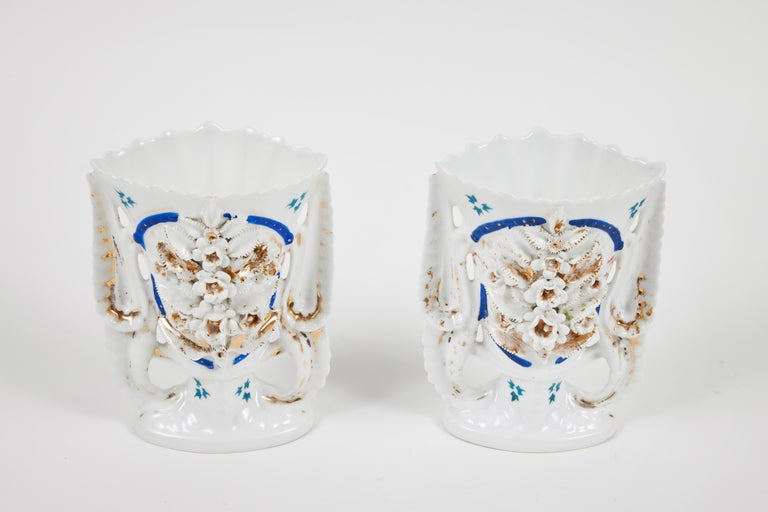 Showcase your flowers in our pair of intricately decorated Victorian porcelain mantel vases. They are meticulously adorned with 3 dimensional flowers, leaves and beaded accents and rim. These vases are white with accents of teal, cobalt and gold. An