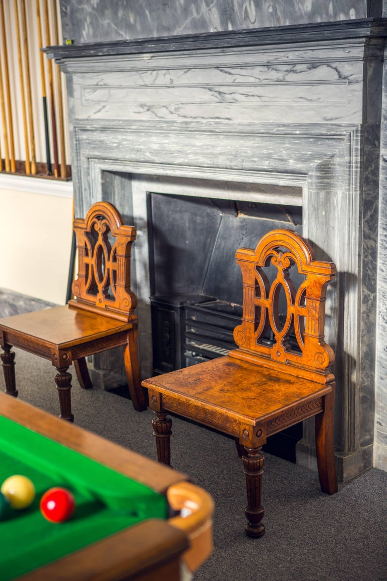 A pair of Victorian Renaissance Revival pollard oak hall chairs The shaped moulded top-rails above pierced scrolling backs and rectangular moulded seats, with guilloche carved seat-rails on reeded turned tapering legs, headed by roundels, on bun