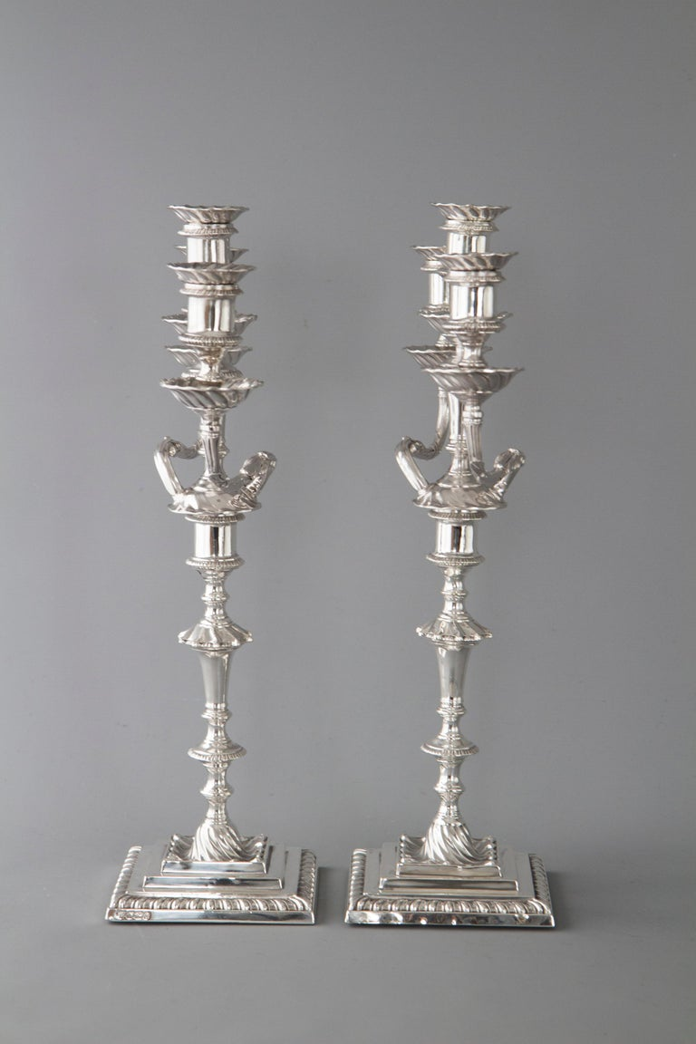 An extremely fine pair of late Victorian silver three-light candelabra. The candlesticks on stepped square section bases with spiral fluted wells. The stem with fluted tapering column, spiral knop and cotton reel capitals with fluted borders. The