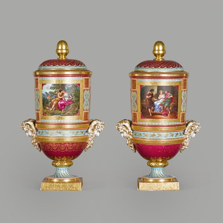 A fine pair of Vienna style covered cylindrical vases, on square footed socle bases.  The vases are decorated with classical scenes including Jupiter and Callisto, after Angelica Kauffman and Bacchus and Ariadne. The vases have satyr head handles
