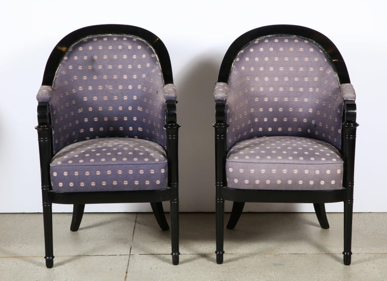 The swooped upholstered back ending in a scroll and supported by a turned column legs.