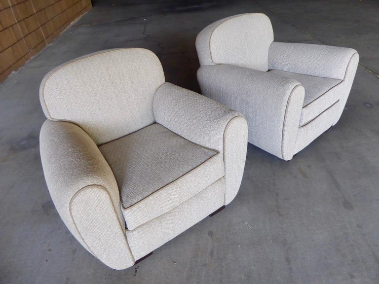 A vintage pair of French Art Moderne club chairs, circa 1930s. Newly reupholstered in a luxurious corduroy style textured fabric with a contrasting piping that provides definition to the entire chair.