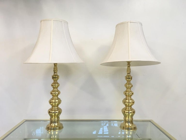 A pair of brass table lamps Original shades 1970s Height with shade is 90cm.