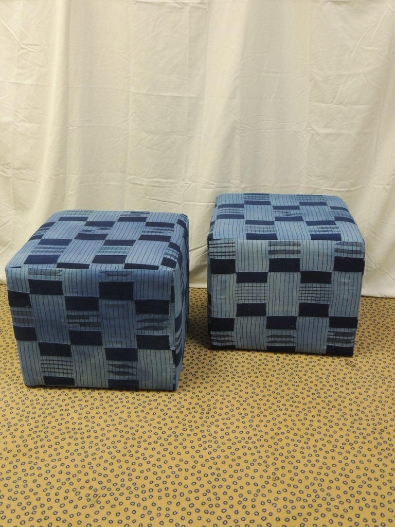 Pair of vintage African blue and indigo woven textile custom square ottomans. Wood frame with padded construction all around and small tack feet. The Yoruba are masters of the indigo-dyeing process. They also have the most varied methods of