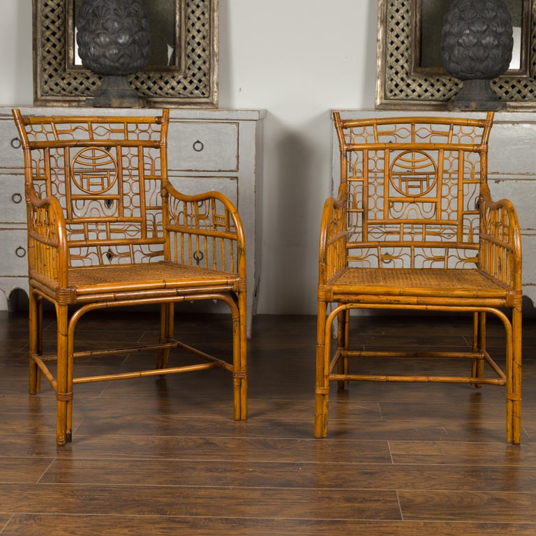A pair of vintage American rattan armchairs from the mid-20th century, with Chinese Chippendale style motifs. Born during the mid-century period, each of this pair of rattan armchairs attracts our attention with its relaxed presence and Chinese