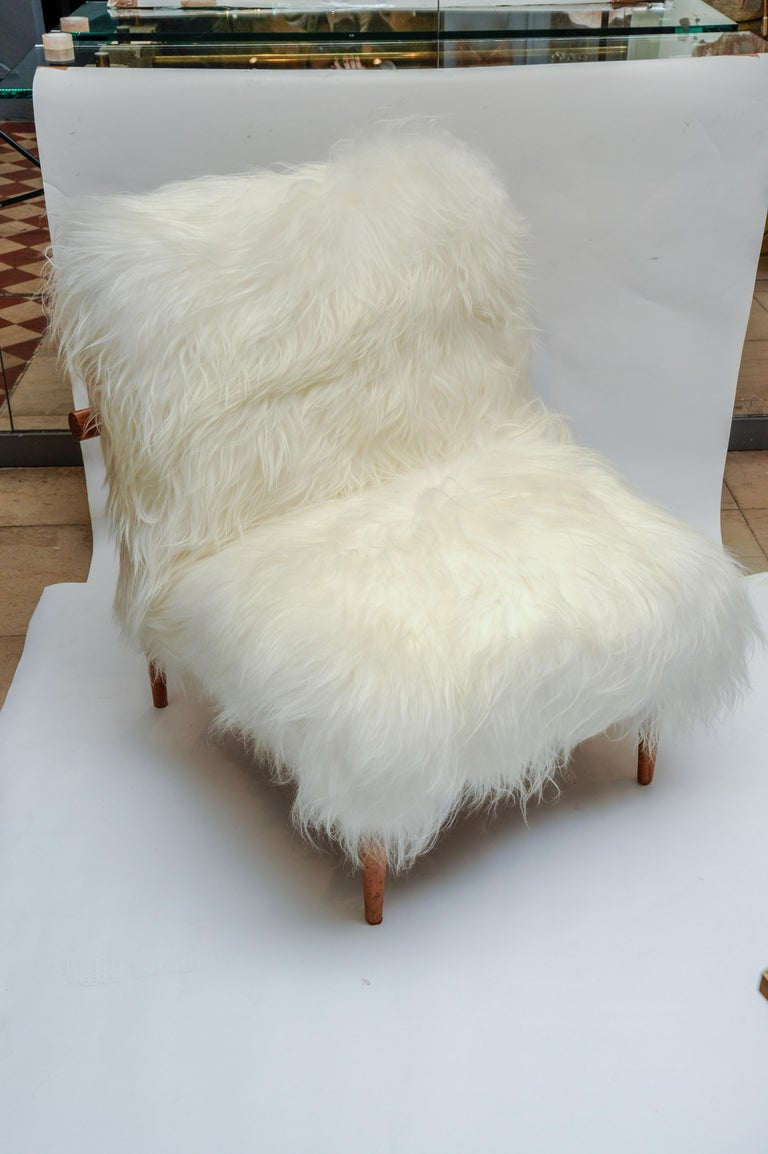 Reupholstered with natural Mongolian goat fur, this pair of armchairs has a Scandinavian 1960s wood structure.