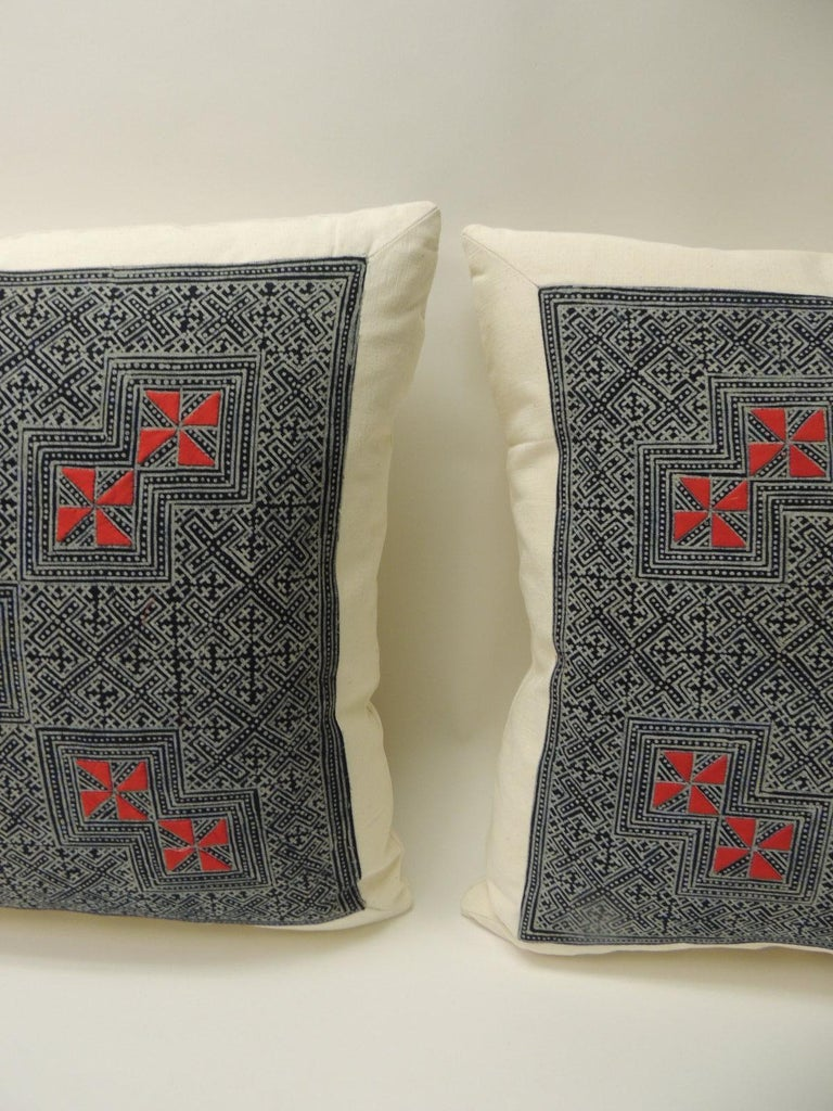 Pair of vintage Asian hand blocked red and indigo square decorative pillows Decorative square pillows handcrafted with a vintage Asian hand blocked batik red and indigo textile. The decorative pillows depict a hand blocked technique in the front
