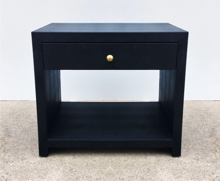 Stunning pair of 1980s nightstands in the style of Karl Springer. Made of solid wood meticulously covered in black shagreen. Clean lines open style with a single top drawer to each and a brass knob with lacquered solid oak interiors over an open