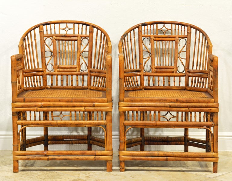 Rising on six legs these intricately crafted iconic armchairs with cane seats feature bamboo frames and Chinese themed bamboo open work inspired by Chippendale design.