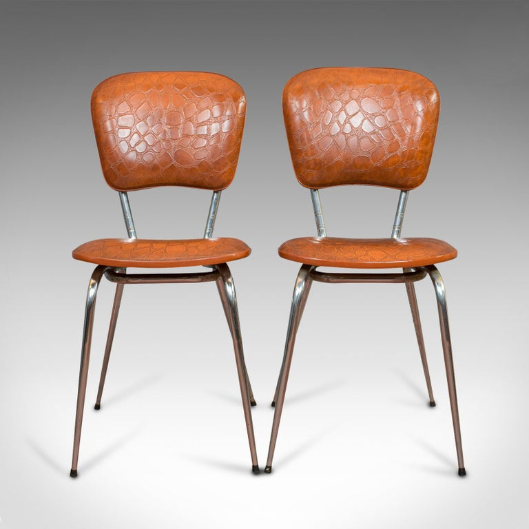This is a pair of vintage chairs. A French, faux crocodile upholstered desk or breakfast chair, dating to the mid-20th century, circa 1960.  Rich tan hues and appealing modern form Displays a desirable aged patina Comfortable, well padded seat