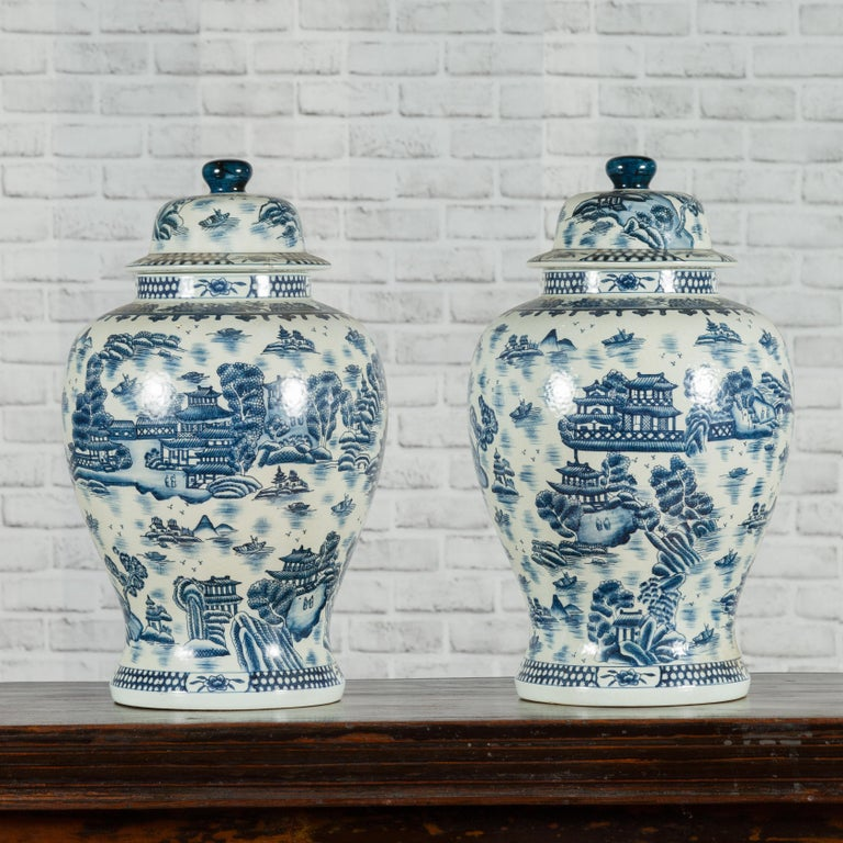 A pair of Chinese vintage blue and white porcelain lidded temple jars from the mid-20th century with landscape and architecture patterns. Created in China during the midcentury period, each of this pair of blue and white porcelain temple jars