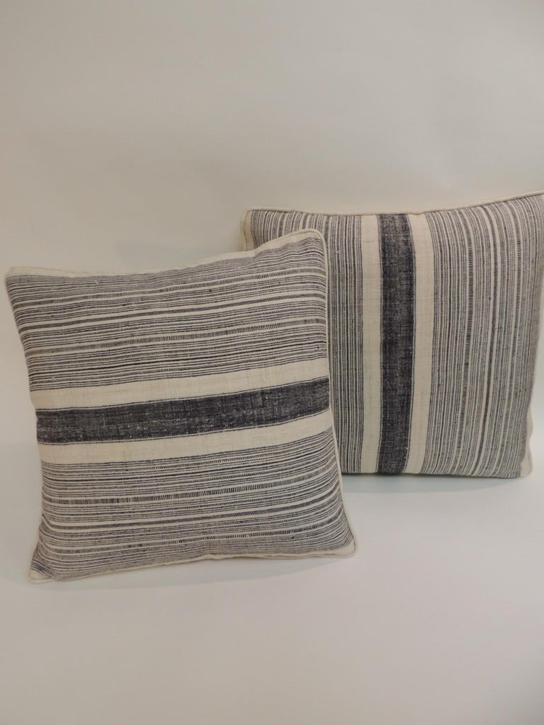 Pair of vintage Chinese Homespun blue and natural stripes decorative pillows. Decorative pillows finished with antique natural linen backing and natural linen self-welt. The Miao are one of several ethnic minorities living in the subtropical