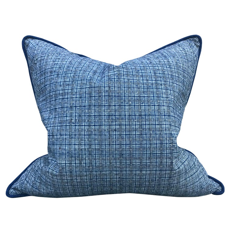 Pair of pillows made from vintage 20th century Chinese plaid cotton panels with a stylized basket weave pattern on one side, and a handwoven indigo cotton panel on the reverse, with a self welt and backed with down.