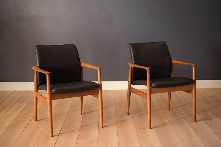 Mid-Century Modern pair of lounge armchairs designed by Grete Jalk for Glostrup Møbelfabrik. This set features sculpted teak arms and a comfortable curved backrest. They have been professionally reupholstered in black leather with brand new foam.