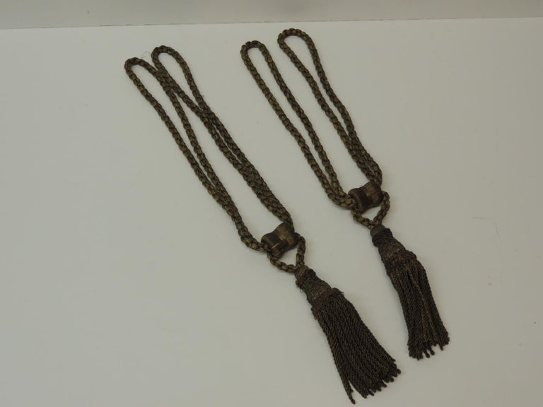 Pair of vintage decorative gold tassels with rope. Curtain tassels with metallic threads on wood. Size: 16