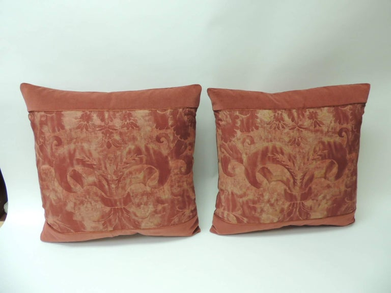 """Pair of vintage Fortuny """"Glicine"""" pattern red and silvery decorative square pillows. Framed with burnt orange cotton velvet and embellished with small silk orange trim at seams. Backed with red cashmere fabric. These pillows were designed using the"""
