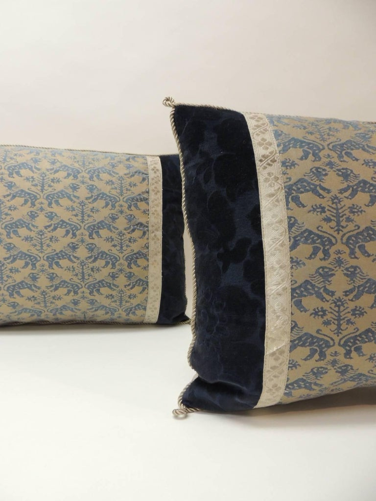 "Pair of vintage Fortuny ""Richelieu"" blue on silver decorative bolster pillows, framed with antique cotton floral velvet and embellished with antique silver metallic tape trim. Accentuated with silk rope trim. Golden silk backings. Decorative pillows"