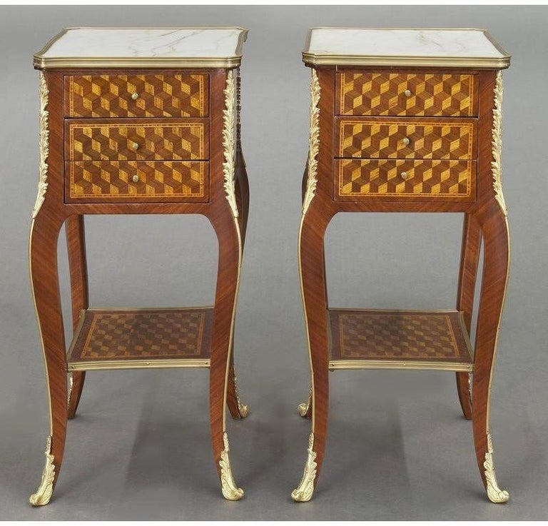 Place this elegant pair of antique nightstands on both sides of a bed for a sophisticated, symmetrical look. Crafted in France circa 1920, each matching bedside table sits on cabriole legs with bronze acanthus leaves at the shoulder. The legs are