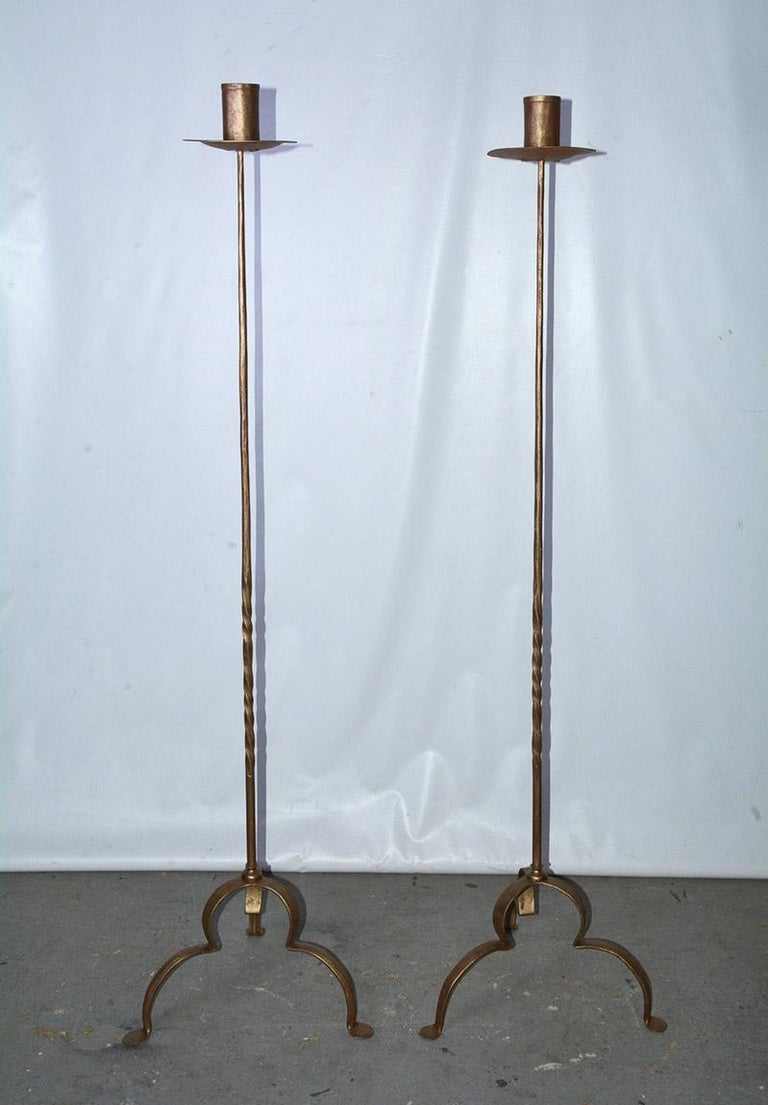 Rustic and elegant, each of the pair of vintage gilt handcrafted wrought iron candleholders or floor torchères has three curved legs, partially twisted decorative shafts and bobeches. The candle sockets have 2