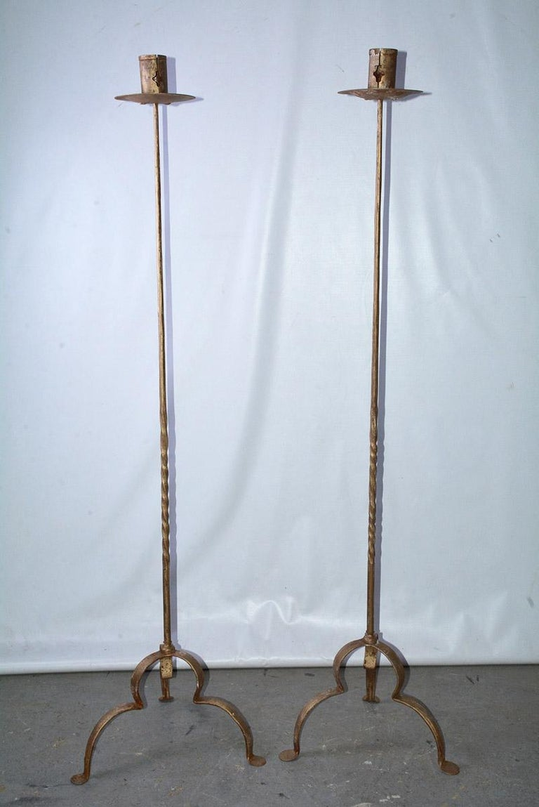 Rustic and elegant, each of the pair of vintage gilt handcrafted wrought iron tall stand candleholders or floor torchières has three curved legs, partially twisted decorative shafts and bobeches. The candle sockets have 2