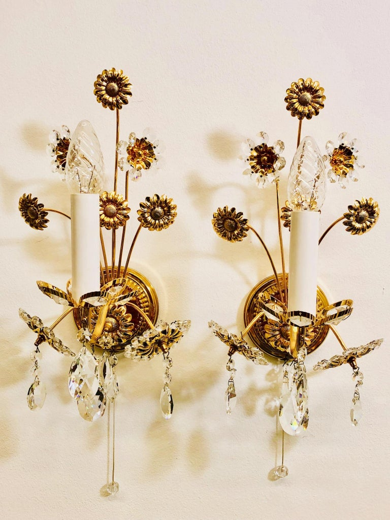 Pair of vintage gold-plated sconces with faceted crystal flowers made by the German company Palwa. Each fixture has one European style E14 socket. It requires a European E14 candelabra bulb, up to 40 Watt.