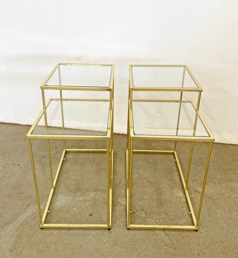 Offered is a pair of vintage tiered end tables with glass tops. These tables have great lines and are sure to class up any joint! Features golden chrome bases with glass tops. Looks like they have three tiers, but the bottoms are missing glass tops.
