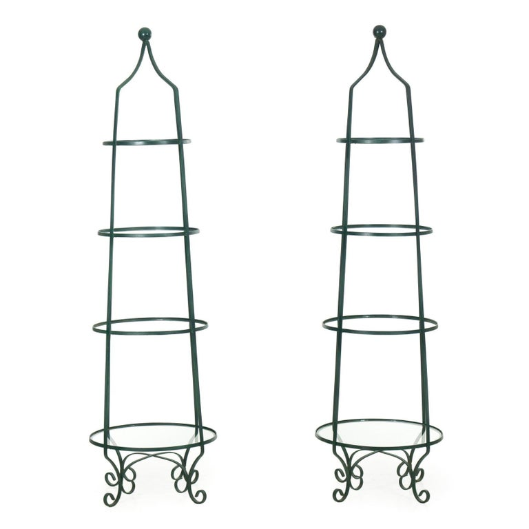 An interesting pair of vintage étagères that we don't see very often, these shelf units are crafted out of curved and welded iron that culminates in a turned metal finial in the crest. The form is tapered with four tiered shelves, each with a glass