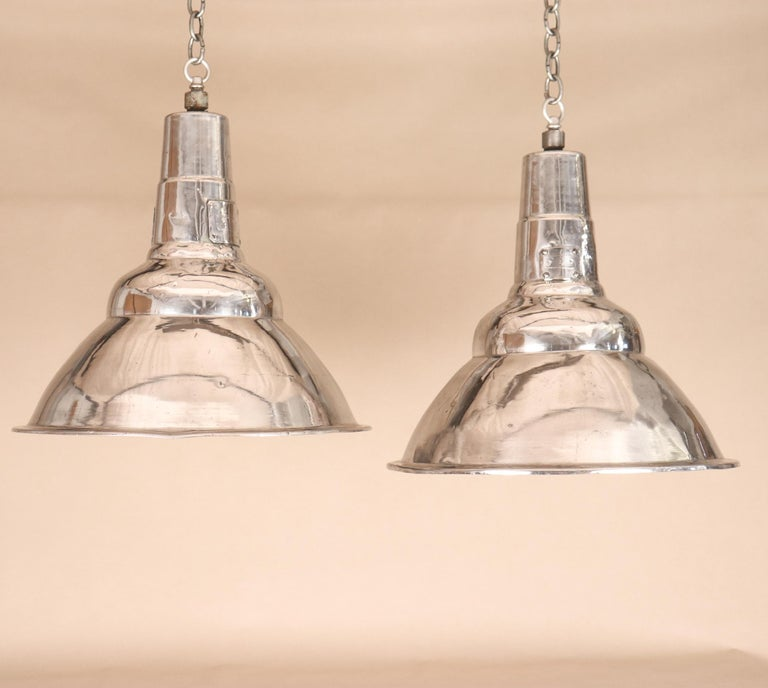 A pair of clean, simple polished aluminum Industrial pendant lights, circa 1960. These vintage floodlights have been newly re-wired with porcelain sockets and disseminate a wide beam, making them ideal over a kitchen island, a game table, or in a
