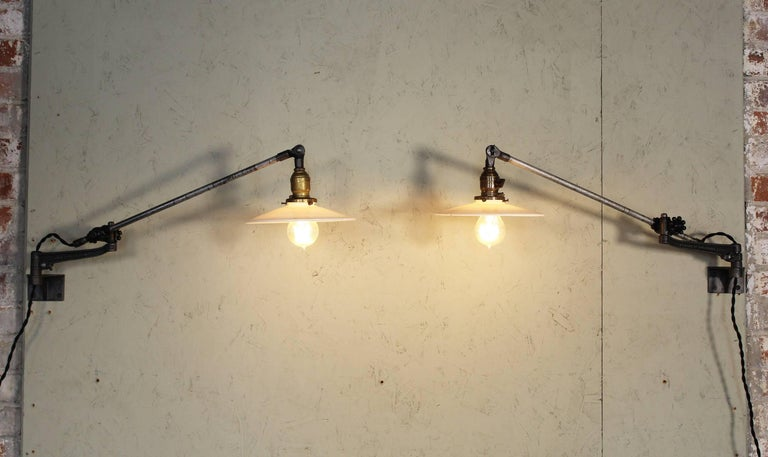 Pair of vintage Industrial milk glass O.C. White wall task lamps, lights with Edison Bulbs. Articulating lamps with cast iron knob adjustment fittings. Milk glass shades measure 9 1/4